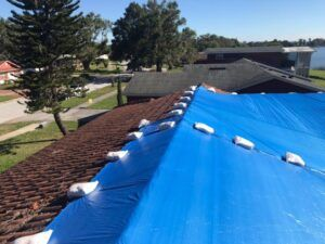 A roof is tarp is secured with sandbags.