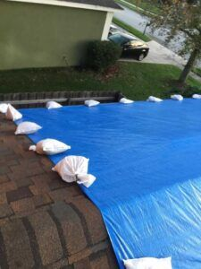 Sandbags secure a tarp without penetrating the roof